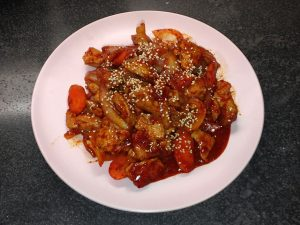 Korean Stir-fried spicy pork dish is served on a pink ceramic plate. The meat and vegetables are redish in color. Small sesame seeds are on top for garnish.