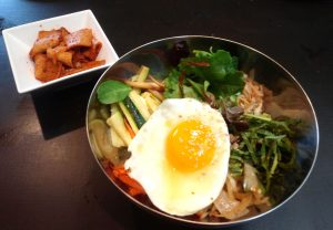 Bibimbap dish with fried egg and side of kimchi