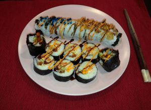 California Roll together with Korean Kimbab roll made with rice, seaweed sheets and other ingredients.