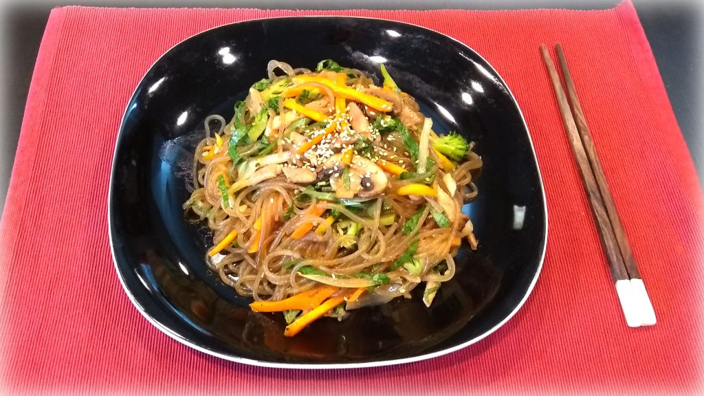 JapChae (잡채) - Korean Stir-fried Sweet Potato Noodles - Dish served with vegetables, meat and sesame seeds for garnish